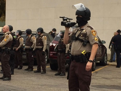law enforcement officer wearing a mask, holding a video camera