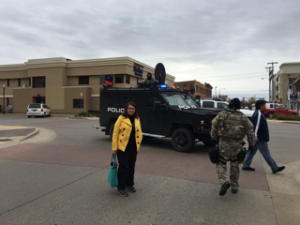Sarah standing in front of law enforcement vehicle